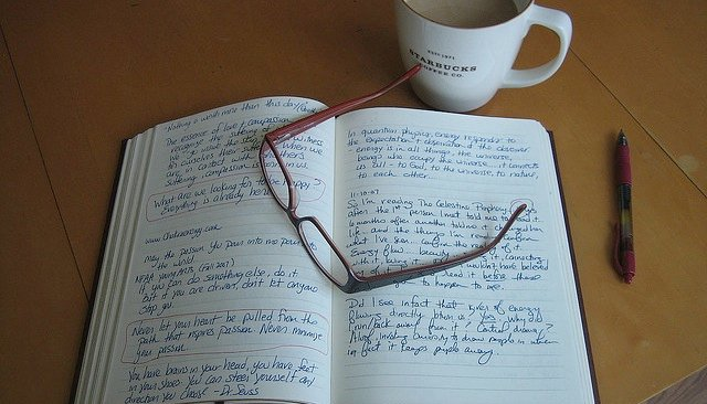 A book on a table with glasses, a pen and a cup of coffee